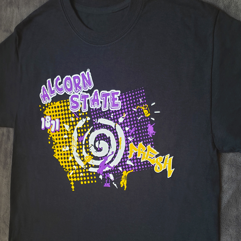 A black t-shirt with Alcorn State 1871 Fresh screen printed on the front. The graphic is speckled with yellow and purple dots, as well as a white sun and paint splatters.